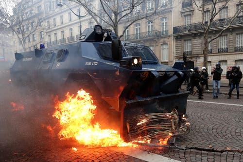 Ein Polizeifahrzeug räumt eine brennende Barrikade weg. (Bild: Ian Langsdon/EPA (Paris, 08.12.2018))