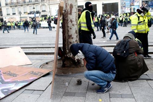 Demonstrierende suchen Schutz. (Bild: Rafael Yaghobzadeh/AP Photo (Paris, 08.12.2018))