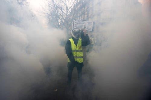 Mitten im Rauch: Ein Anhänger der Gelbwesten hält ein Schild hoch. (Bild: Ian Langsdon/EPA (Paris, 08.12.2018))