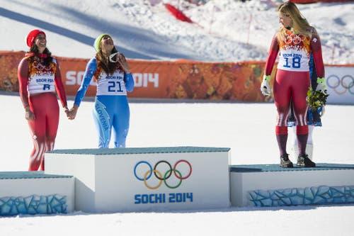 Lara Gut wartet bei der Siegerehrung auf Dominique Gisin (links) und Tina Maze, die ex-aequo bei den Olympischen Spielen in Sotschi Abfahrtsgold holen. (Bild: Keystone)