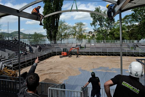 Arbeiter bringen einen Quermasten oberhalb der VIP-Tribüne an. (Bild: Nadia Schärli)