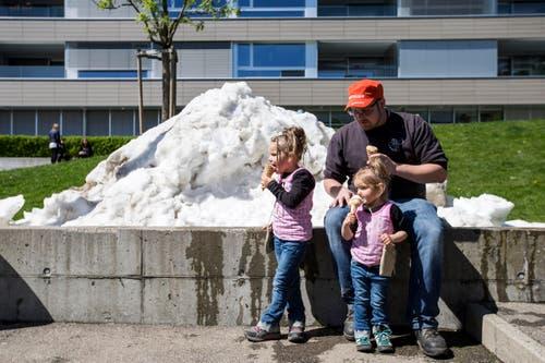 Jamie, Yael und Martin essen ein Eis vor einem Schneehaufen (Bild: Alexandra Wey / Keystone (Baar, 30. April 2017))