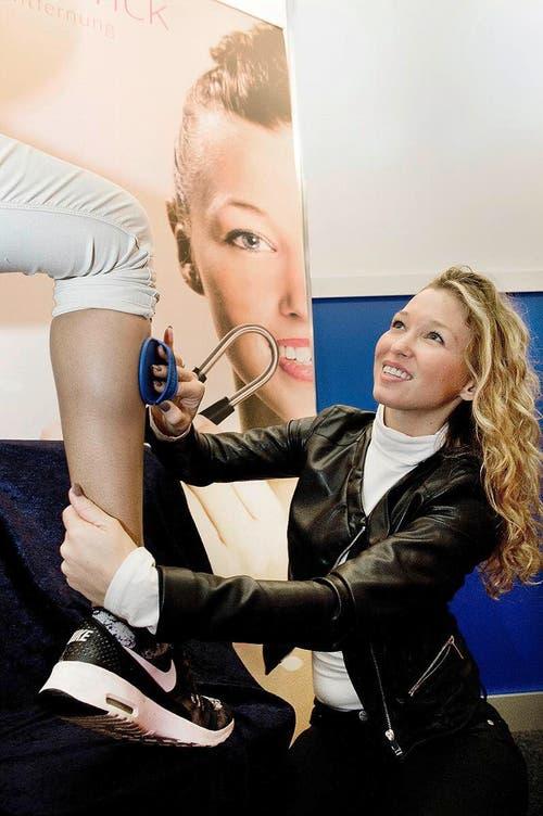 Messeverkäuferin Cindy Kullack demonstriert ihr Wundermittel am Bein einer Kundin: den Haarentfernungshandschuh. (Bild: Eveline Beerkircher / Neue LZ)