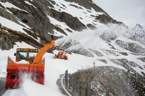 Bei trübem Wetter fräsen sich die Arbeiter mit ihren Maschinen durch die Schneemassen. (Bild: Keystone / Urs Flüeler)