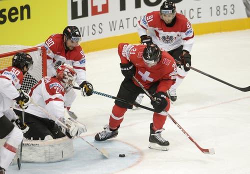 Der Schweizer Kevin Fiala (zweiter von rechts) plant einen Schussa aufs Goal während der Goalie der Österreicher Bernhard Starkbaum versucht (zweiter von links) ihn zu blocken. (Bild: Keystone / Petr David Josek)
