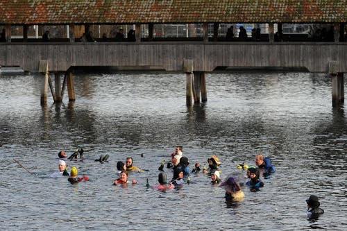 Eine Traube von Silvesterschwimmern treibt unter der Kapellbrücke durch Richtung Reussbrücke. (Bild: Boris Bürgisser / Neue LZ)