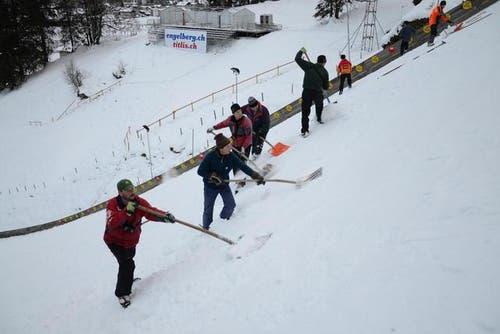 Steigeisen an den Füssen ermöglichen den Männern vom Engelberger Schanzenteam einen sicheren Halt im steilen Gelände der Aufsprungbahn der Titlis-Schanze in Engelberg. (Bild: PD / Beat Christen)