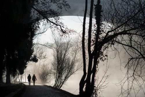 Spaziergänger laufen in Bern der Aare entlang. (Bild: Keystone / Alessandro della Valle)