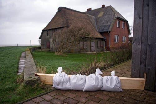 Auf der Hallig Langeness in Deutschland sollen Sandsäcke ein Wohnhaus schützen. (Bild: Keystone)