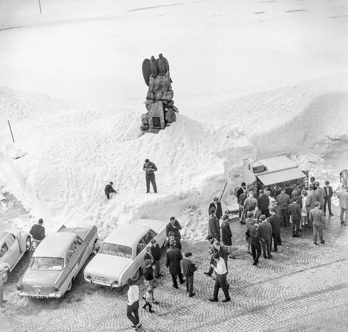 Autofahrer machen bei noch winterlichen Verhältnissen am 26. Mai 1963 einen Halt auf der Passhöhe am Gotthardpass und versorgen sich bei einem Kiosk-Häuschen unterhalb des Fliegerdenkmals für den seinerzeit hier abgestürzten Waadtländer Fliegeroberleutnant Adrien Guex. (Bild: Keystone)