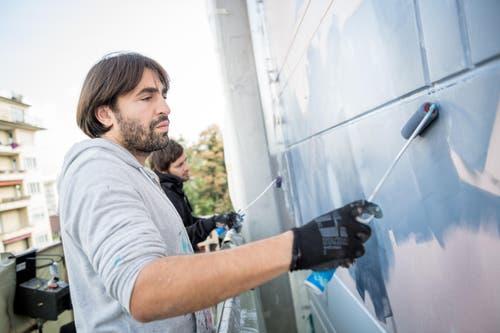 Die Künstler Christian Rebecchi (vorne) und Pablo Togni verpassen dem Neubad einen neuen Anstrich. (Bild: Roger Grütter)
