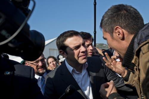 Der griechische Premierminister Alexis Tsipras, Mitte, unterhält sich mit einem Flüchtling. (Bild: AP/Marko Drobnjakovic)