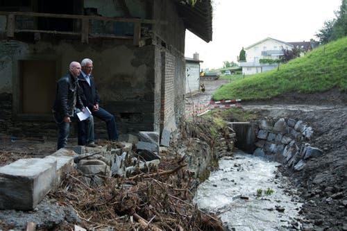 Gemeindepräsident Hans Burri begutachtet mit unserem Reporter Roger Rüegger den Götzenpfalbach. (Bild: Dominik Wunderli (Neue LZ))