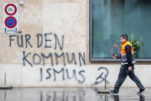 """Zürich: Ein Mann läuft vor einer versprayten Fassade auf der steht """"Für den Kommunismus"""" beim traditionellen 1. Mai-Umzug. (Bild: Keystone)"""