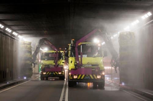 Zwei Lastwagen putzen die Wände im Gotthard-Strassentunnel. (Bild: Keystone / Alexandra Wey)