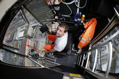 In der Regel schaut Kranführer Peter Linhart konzentriert nach unten - auf die Park-Tower- Baustelle. Für den Fotografen macht er eine Ausnahme. (Bild: Stefan Kaiser / Neue ZZ)
