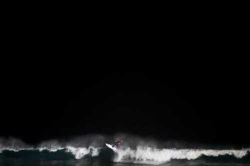 Ein Surfer während des Nachtwettkampfs in Ashdod im Süden von Israel. (Bild: AP / Oded Balilty)