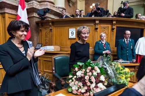 Bundesrätin Eveline Widmer-Schlumpf empfängt Applaus von Kollegin Doris Leuthard, links, und den Mitgliedern der Sitzung der Vereinigten Bundesversammlung. (Bild: KEYSTONE / LUKAS LEHMANN)