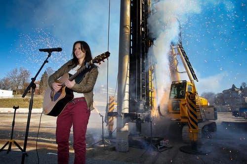 Caroline Chevin; im Hintergrund das Feuerwerk und die Bohrung des ersten Pfahls. (Bild: Philipp Schmidli / Neue Luzerner Zeitung)