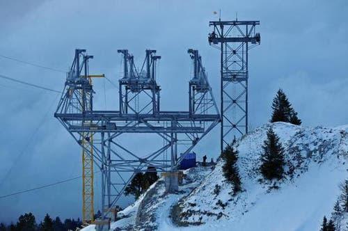 16. Januar: Eine der vier neuen Stützen (die erste unterhalb der Bergstation) für die Cabrio Bahn. Rechts eine Stütze der alten Luftseilbahn, die abgebrochen wird. Links verläuft die Transportseilbahn Richtung Kälti. (Bild: Robert Hess / Neue OZ)