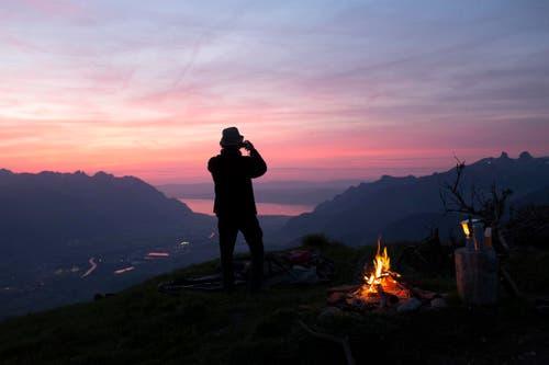 Ein Berggänger fotografiert den Sonnenuntergang in Bex / VD, im Hintergrund die Rhône-Ebene und der Genfersee. (Bild: Keystone / Anthony Anex)