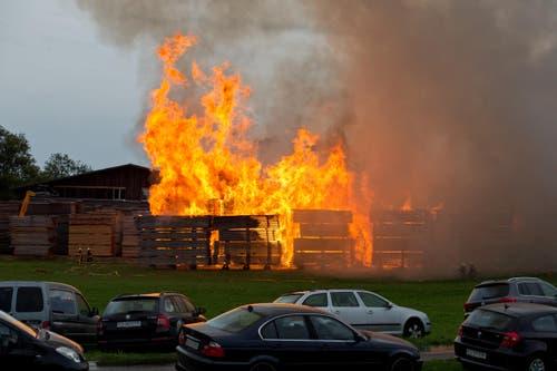 Die brennende Sägerei von aussen gesehen. Zuvorderst: Unzählige Autos, deren Fahrer zum Brand ausrückten. (Bild: Dominik Wunderli / Neue LZ)