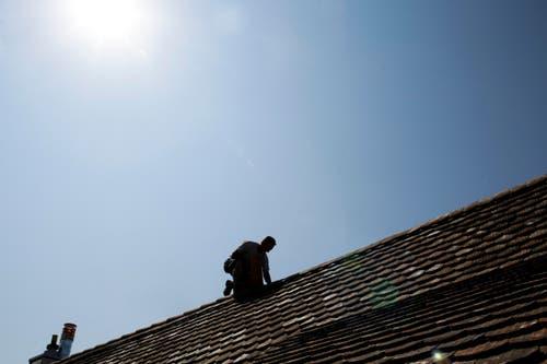 Noch ein Hitzeberuf - weit und breit kein Schatten in Sicht: Marek Markovic repariert in der Sommerhitze ein Dach in Gottlieben. (Bild: Donato Caspari)