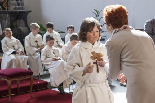 Alexander Niederberger erhält von Berta Christen das Holzkreuz zur Erstkommunion in Wolfenschiessen (Bild: Edi Ettlin)