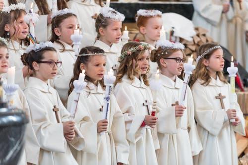 Die Mädchen tragen Blumenkopfschmuck und Kerzen bei der Erstkommunion in Sempach. (Bild: Roger Grütter / Neue LZ)