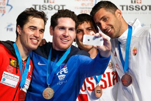 Selfie der Sieger: Gauthier Grumier mit Silbermedaillengewinner Max Heinzer, links, dem Russen Pavel Sukhov und Gabor Boczko (ganz rechts). (Bild: Keystone / Valentin Flauraud)