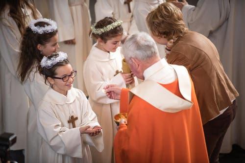 Die Kinder erhalten ihre erste Hostie. (Bild: Roger Grütter / Neue LZ)