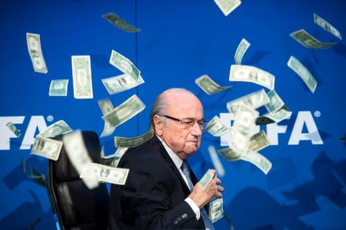 An einer Medienkonferenz der Fifa wird deren Präsident Sepp Blatter mit Banknoten beworfen (20. Juli). (Bild: Keystone / Ennio Leanza)
