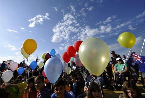 Menschen halten Luftballone an der Eröffnung (Bild: Keystone)