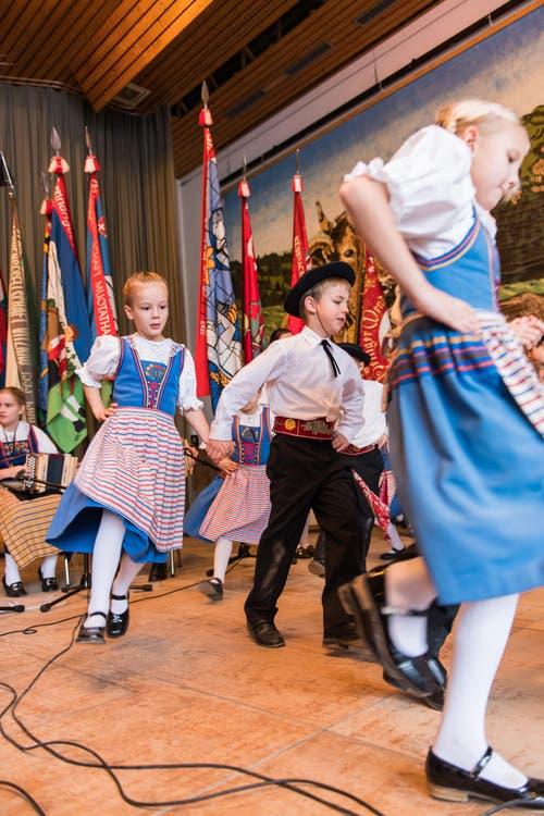 Kinder von der Kindertrachtengruppe Weggis tanzen vor vollen Rängen in der Turnhalle. (Bild: Roger Grütter (LZ))