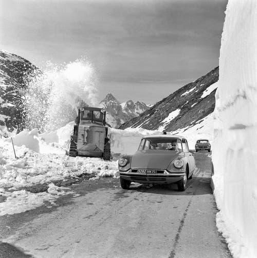 Schneeräumung auf dem Simplonpass, aufgenommen im April 1960. Ein Auto der Marke Citroen DS passiert eine Schneeschleuder. (Bild: Keystone)