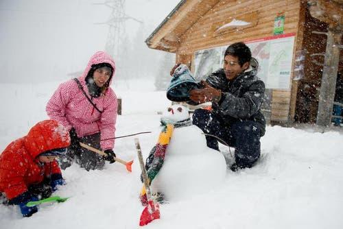 Ron und Stefanie Giger bauen zusammen mit Ronny Asenico (von links) einen Schneemann auf dem verschneiten Langis. (Bild: Corinne Glanzmann)