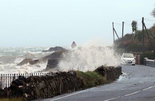Wellen peitschen gegen die Küstenstrasse im nordirischen Antrim. (Bild: Keystone)