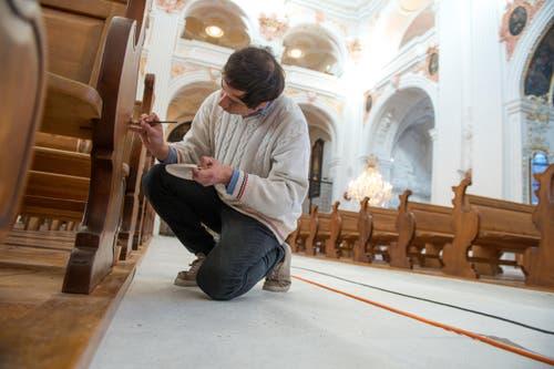 Paulo Russo retuschiert die Kirchenbänke mit Ölfarbe. (Bild: Dominik Wunderli)