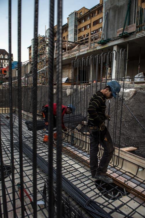 Zwei Bauarbeiter legen Armierungseisen für das Fundament und die Kellerwände. (Bild: Nadia Schärli (LZ))