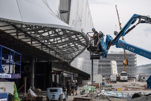 Die Wölbung ist der Eingang: Ein Arbeiter in der Hebebühne bei der Montage. (Bild: Nadia Schärli/LZ)