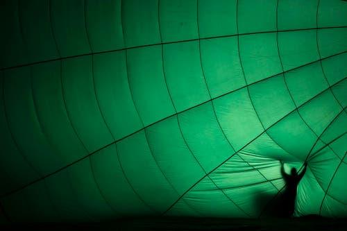 Ein Heissluftballon wird vor dem Start bei den 37. Internationalen Luftballon-Wetttbewerben in Château d'Oex aufgeblasen. (Bild: Keystone / Valentin Flauraud)