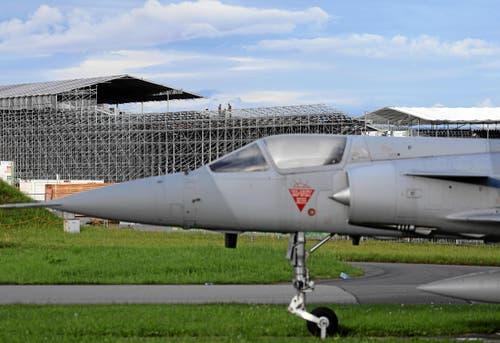 Eine ausgemusterte Mirage III steht beim Eingang zum Militärflugplatz Payerne und sorgt für einen Kontrast zur grossen Stahlarena im Hintergrund. (Bild: Swiss Image / Andy Mettler)