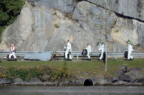 23. Oktober 2013: Ein F/A-18 Kampfjet ist bei Alpnach Dorf abgestürzt. Das Bild zeigt Spezialisten der Schweizer Armee und Polizeiforensiker bei der Untersuchung von Wrackteilen am Unfallort. (Bild: Keystone)
