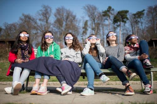 20. März: Sechs junge Frauen folgen nicht etwa einem neuen Modediktat, sondern verfolgen in Zürich mit Schutzbrillen das Naturspektakel der partiellen Sonnenfinsternis. So richtig dunkel wird es aber nur über dem Nordatlantik, auf den Färöerinseln und in Spitzbergen. (Bild: Keystone /Ennio Leanza)