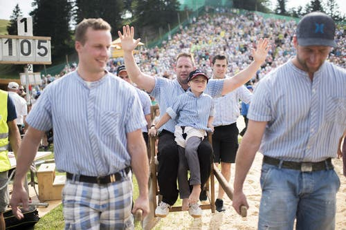 Zum Abschied von Adriean Laimbacher tragen ihn Kollegen in einer Sänfte um den Schwingplatz. (Bild: Keystone / Ennio Leanza)