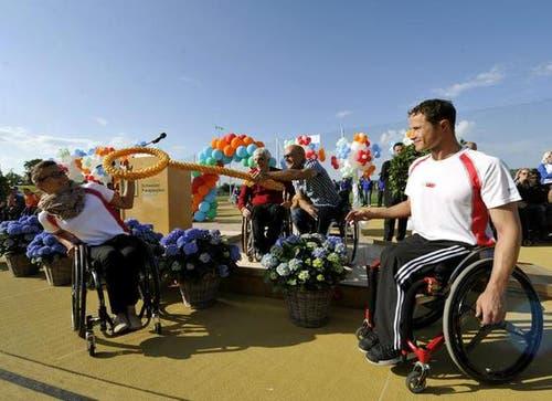 Daniel Joggi, Präsident des Stiftungsrates der Schweizer Paraplegiker-Stiftung (hinten links) und Heinz Frei (hinten rechts) übergeben den symbolischen Schlüssel an Manuela Schaer und Marcel Hug. (Bild: Keystone)