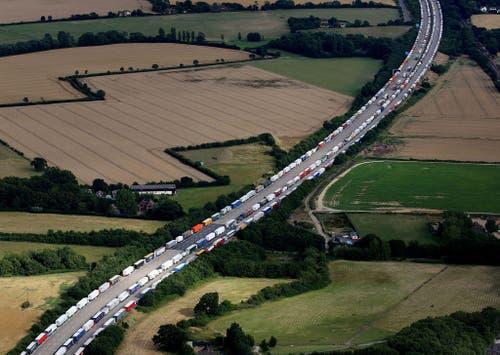 29. Juli: Hunderte von Flüchtlingen versuchen Nacht für Nacht, auf teilweise halsbrecherische Art von Frankreich nach England zu gelangen. Wegen verstärkten Kontrollen in Südengland stauen sich deshalb die Lastwagen auf der Autobahn. (Bild: Gareth Fuller via AP)