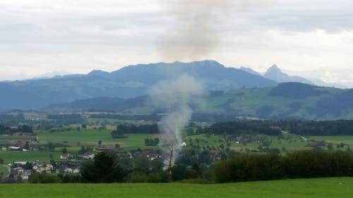 Der Brand aus der Optik des näherfahrenden Fotografen: Es steigt eine Rauchsäule in den Himmel. (Bild: Dominik Wunderli / Neue LZ)