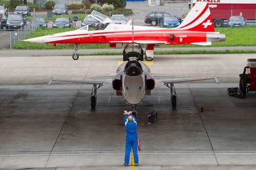 Ein Techniker macht einem Piloten Zeichen im Hangar des Flugplatz Emmen. (Bild: Keystone)