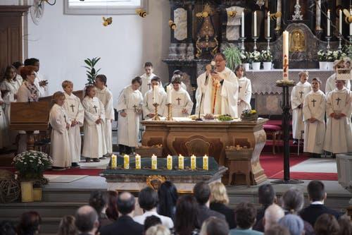 Pfarrer Erich Lehmann hebt inmitten der Erstkommunionkinder in Wolfenschiessen Wein und Brot. (Bild: Edi Ettlin)